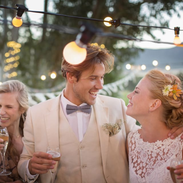 Young couple and their guests with champagne flutes during wedding reception in garden