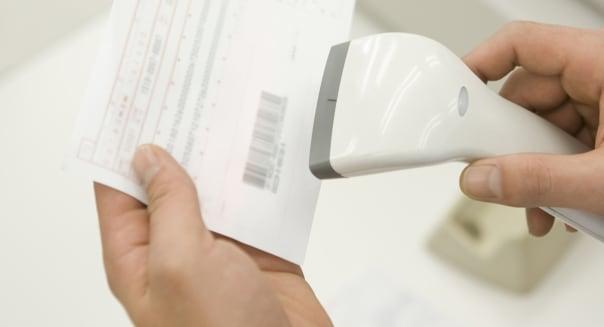 Store clerk scanning barcode on bill