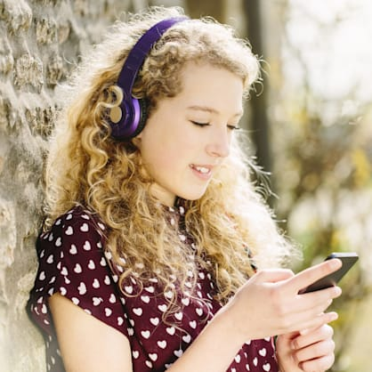 Portrait of teenage girl in village with headphones and smartphone