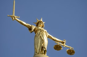 Close-up of the statue of Lady Justice, holding a sword and the scales of justice, located on top of the dome above the Old Bail