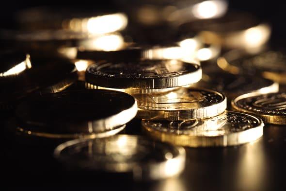 Golden coins on black background. Macro shot.