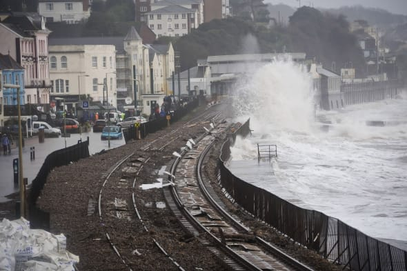 Composite image with file photos dated 05/02/14 (top) and image dated 12/03/14 (bottom) showing a before and after of the damage and subsequent repairs to the sea wall and railway line at Dawlish in Devon, as the storm-wrecked railway line is due to reopen as planned at the end of this week, Network Rail (NR) has confirmed. PRESS ASSOCIATION Photo. Issue date: Monday March 31, 2014. The coast-hugging stretch of line was first severely damaged in this winter's savage storms and damaged again in another violent storm on February 14. With the line shut and round-the-clock work going on to bring it back into service, a  massive landslip, involving the collapse of 20,000 tonnes of cliff-face near Teignmouth on March 4, had threatened the planned re-opening. But NR said today the reopening - on Friday - was going ahead. NR chief executive Mark Carne said: