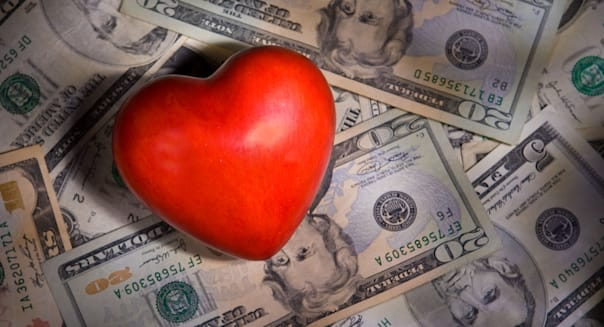 B4NFMT A Heart with Money photo Illustration with dramatic light. Investing with your heart concept. Charity and philanthropy.