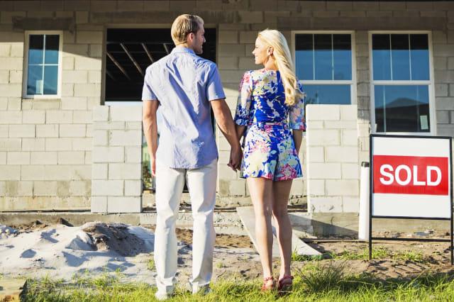 Caucasian couple admiring new home