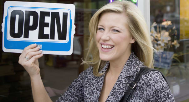 Smiling woman with an open sign