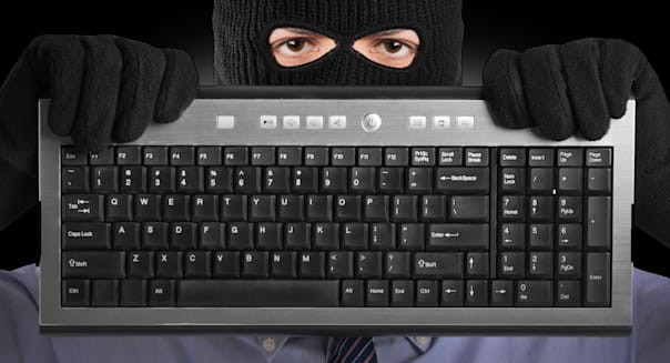 BYRP3Y A hacker with robbery mask holding a keyboard scam email scammer scammed computer scam adult; background; bandit; black;