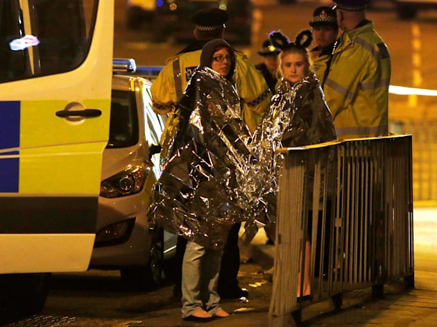 Concert-goers wrapped in thermal blankets stand outside the Manchester Arena, where US singer Ariana...