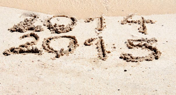 New Year 2015 is coming concept - inscription 2014 and 2015 on a beach sand, the wave is starting to cover the digits 2014
