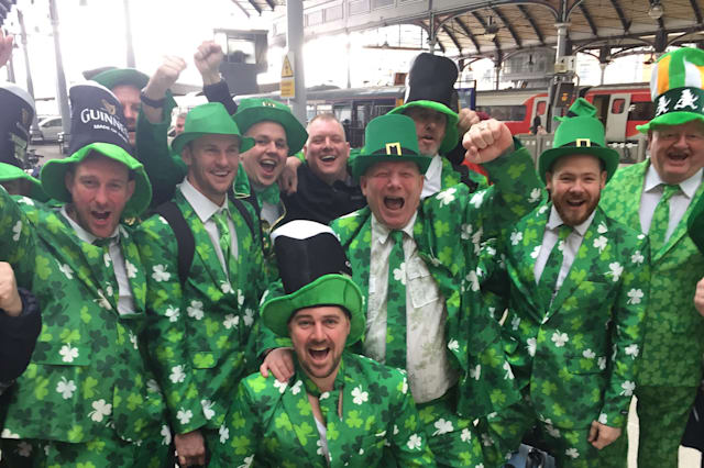 A group of men dressed in green suits on St Patrick's Day at Newcastle railway station.