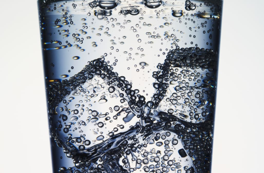 Close up of seltzer water and ice in glass