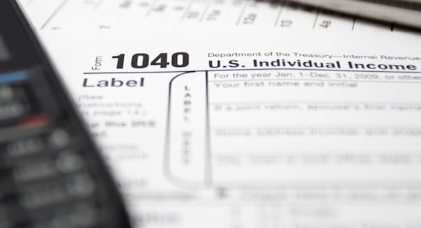Tax forms, mobile phone and pen