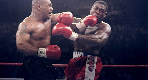 Mike Tyson lands a left on Frank Bruno of Great Britain