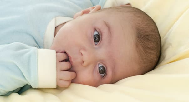 Portrait of a cute baby lying on a bed.