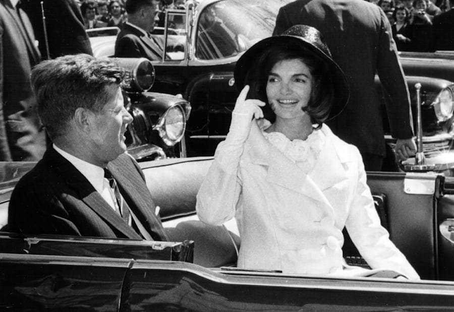 President John F. Kennedy and First Lady Jacqueline Kennedy ride in a parade March 27, 1963 in Washington,