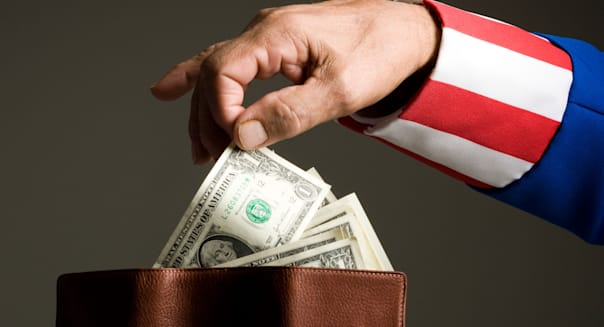 BJTFW1 Man in Uncle Sam's costume taking money from wallet, studio shot  Man; in; Uncle; Sam's; costume; taking; money; from; Se