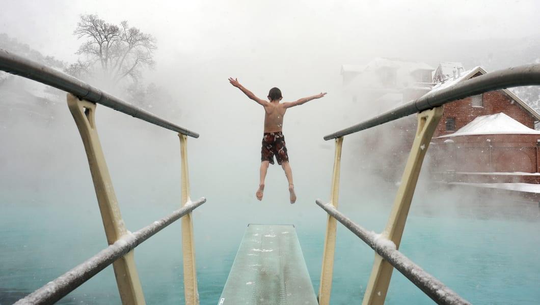 GLENWOOD06-- Erik Feiereisen, 8, of Boulder, dives into the pool through the rising steam at the Glenwood Hot Springs. The Glenw