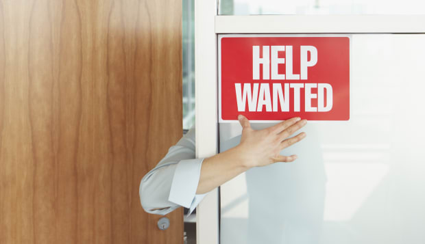 Businesswoman reaching for ?Help Wanted? sign