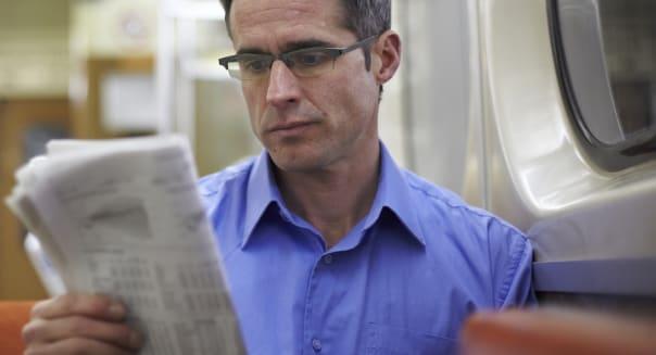 Man Reading Newspaper On Subway