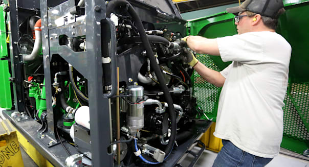 FILE - In this Feb. 11, 2015, file photo, Mark Moriarty works on a John Deere Tracked Feller Buncher/Harvester at John Deere Dubuque Works in Dubuque, Iowa. The Commerce Department reports on U.S. factory orders for June 2015 on Tuesday, Aug. 4, 2015. (Jessica Reilly/Telegraph Herald via AP) MANDATORY CREDIT