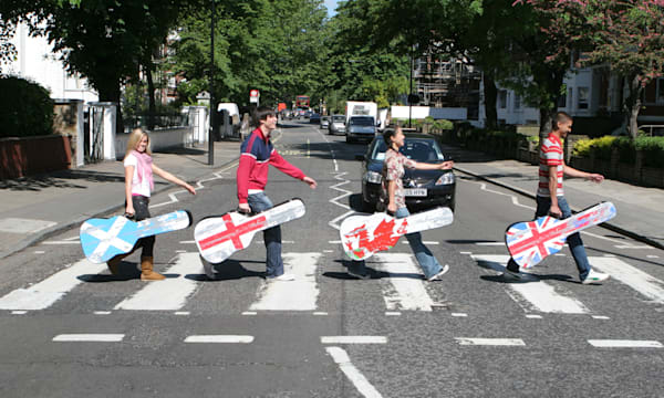 Four people carrying guitar cases on the Abbey Road pedestrian crossing in London, made famous by The Beatles in the 1960s, St J