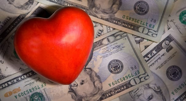 A Heart with US Money photo Illustration with dramatic light. Investing with your heart concept. Charity and philanthropy.
