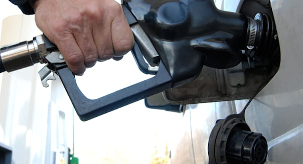 Close up of a customer's hand pumping fuel into car's gas tank.