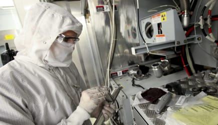 A worker prepares a silicon wafer machine in a clean room at