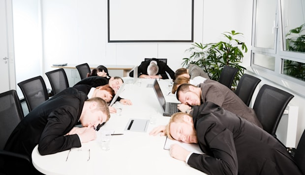 Businessmen and Women Sleeping in Boardroom Meeting