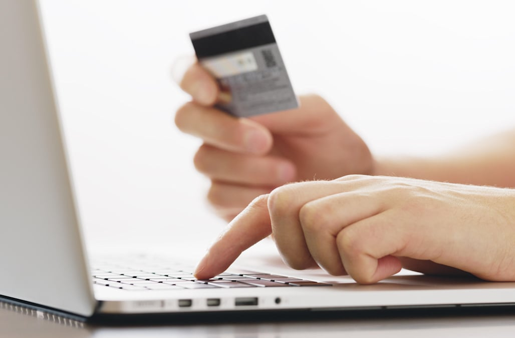 human  holding credit card and using laptop. Online shopping