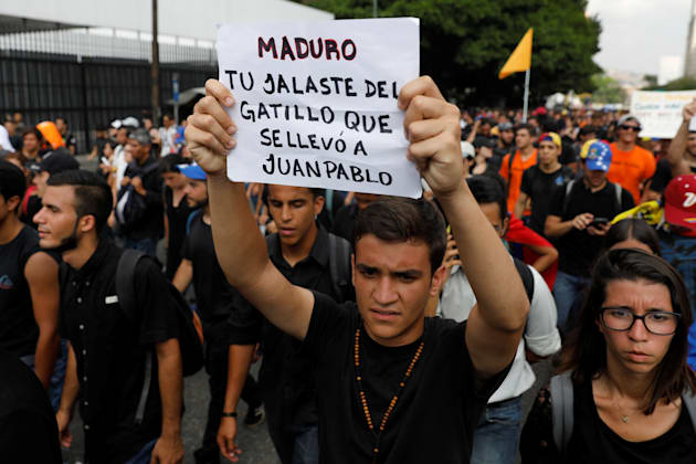 """A student holding a sign that reads, """"Maduro, you pulled the trigger that took to Juan Pablo"""",..."""