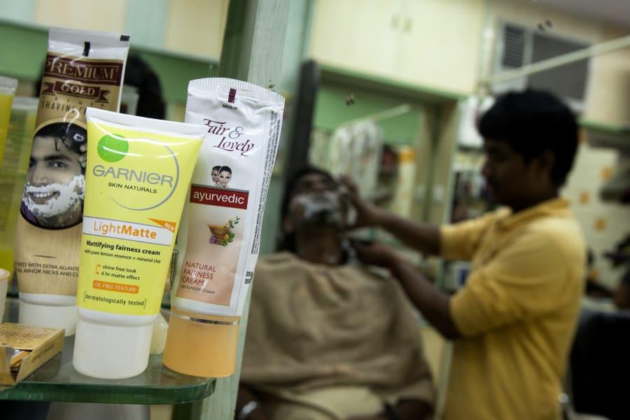 Productos para aclarar la piel son ofrecidos en un estante mientras afeitan a un hombre en un salón en...