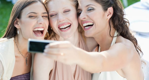 Three women at an outdoor party taking a self-portrait with a digital camera smiling