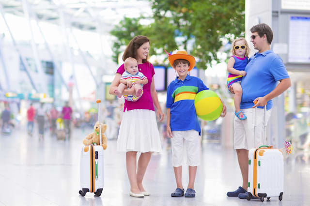 Big happy family with three kids traveling by airplane at Dusseldorf International airport, parents with teenager boy, toddler g