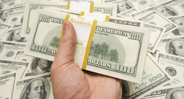 Hand holding american dollars against money background