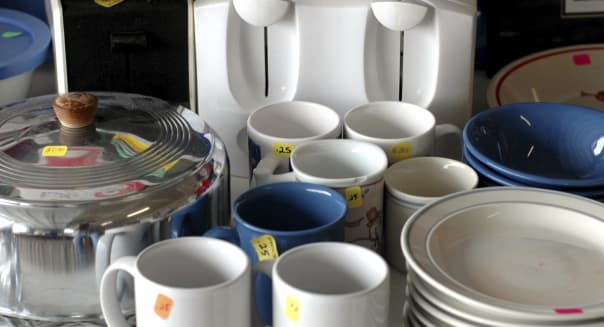 A group of dishes at a yard sale.