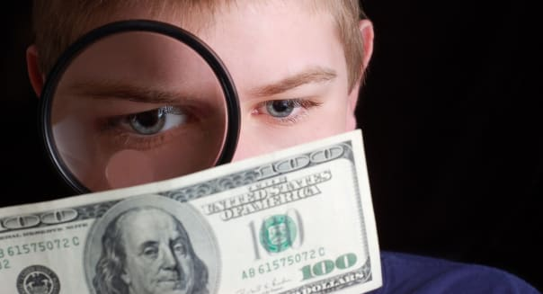 A young man anayzing his money or his finances (shallow DOF with focus on eyes).