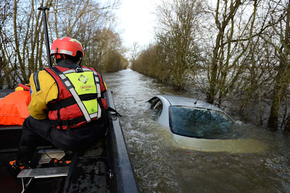 File photo dated 26/01/14 of members of the Avon and Somerset Police Underwater Search Unit inspecting a submerged abandoned car as they head to the village of Muchelney in Somerset, the car owned by Mr Zajaczkowski  has been sold for more than 100,000 pounds on Ebay. PRESS ASSOCIATION Photo. Issue date: Thursday March 20, 2014. The unnamed bidder paid ?101,100 on the online auction site to buy the Seat Toledo after it was put up for sale by owner Hubert Zajaczkowski, 21. Mr Zajaczkowski is donating the cash to a charity helping the victims of flooding in Somerset. See PA story ENVIRONMENT Floods Car. Photo credit should read: Andrew Matthews/PA Wire