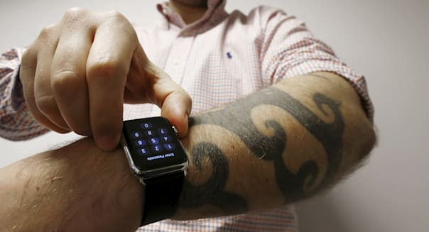 Reuters journalist Matt Siegel inputs his passcode onto his Apple Watch as his tattoos prevent the device's sensors from correctly detecting his skin, in Sydney, Australia, April 30, 2015.  REUTERS/Jason Reed