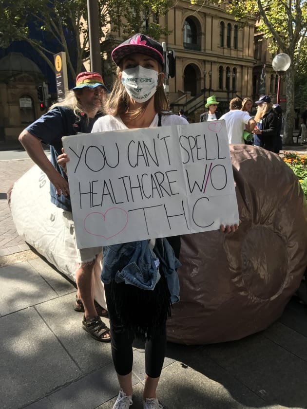 A protester stands across the road from NSW parliament on Tuesday to demand better access to medical