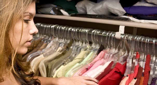 Woman searching through her closet looking for clothes