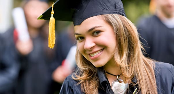 BBY7A0 graduation woman smiling and looking happy outdoors  graduation; woman; smiling; looking; happy; outdoor; graduation; wom