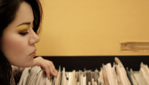 Young secretary looking through papers in office
