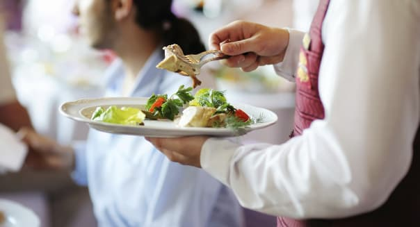 Plate with meal in waiter's hands