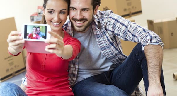 Young couple  taking selfies in their new home