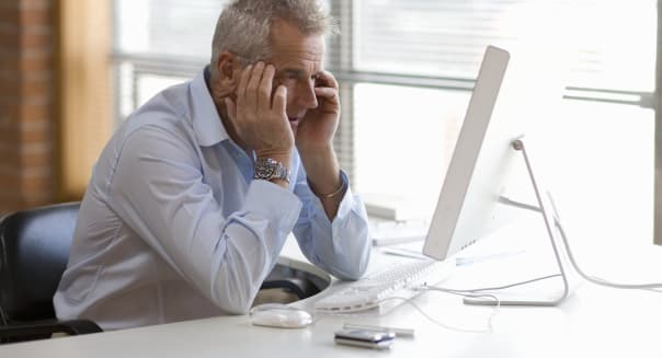 Senior businessman sitting at  computer holding hands to head