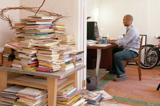 Man working in home office by bikes and books piled by doorway, mess,  messy, clutter, houseCasual Clothing, Horizontal, Full L