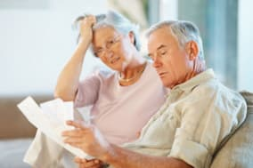 BHYT6R Elderly man with his wife going through documents on couch. Image shot 2009. Exact date unknown. Mistakes Retirees Make b