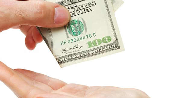 Mans hand giving hundred dollars to female hand, isolated on white