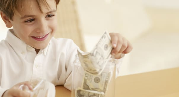 Boy putting money into a cookie jar.Keywords:  People, Security, Happiness, Home Interior, Jar, Wealth, Business, Finance, Pape
