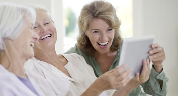 Older women using digital tablet on sofa